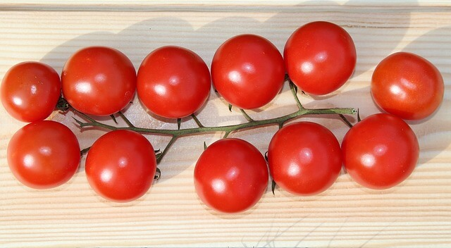 A cluster of 11 red cherry tomatoes on a wooden table